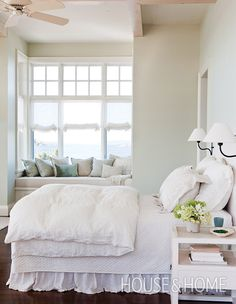 A pale palette keeps the look of this bedroom light and airy, while a window seat overlooking the Georgian Bay is the perfect spot for reading. | Photographer: Ted Yarwood | Designer: Melody Duron