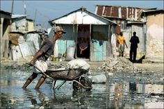 A resident of Fort Dimanche, a former political prison now renamed Democracy Village, pushes a wheelbarrow through rain water mixed with sewage.