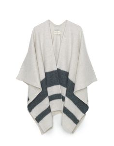Luxurious poncho in extra soft, boiled llama wool with stripe detail at the bottom. Oversized fit. Inside tape edgeing.