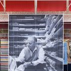 A large-scale photo of Girard greets visitors to the exhibition space. At left is a display case devoted to the short-lived Textiles &...