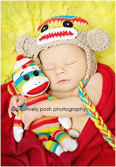 Sweet newborn baby boy in sock monkey hat, photographed by Positively Posh Photography