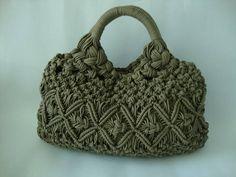 Bolsa de macramé confeccionada em cordão encerado na cor ráfia, forro em cetim, fechamento com botão imantado. R$ 210,00