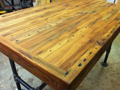 Reclaimed industrial kitchen island/dining table featuring antique barnwood butcher block and steel pipe base.
