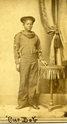 """This photo of Robert Walker, a young African American, """"First Class Boy""""  dressed in a sailor's uniform, has """"Our Bob"""", written on the bottom."""
