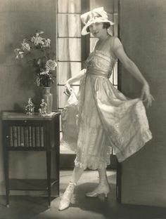 Photo, ca.1921, Baron de Meyer.  Irene Castle Treman wearing a light taffeta dress over an underskirt in cream tulle and Valenciennes lace, by Lucile, with a hat in lace with flowers.