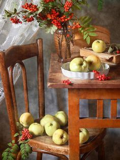 http://pixels.com/products/rowan-berries-and-autumn-apples-nikolay-panov-art-print.html Rustic still life photography with branches of rowan tree with red berries and a lot of scattered fresh autumn green and yellow apples on old vintage table and wooden chair in country house early in fall