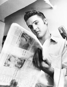 Elvis killing time perusing the newspapers before his evening's scheduled performance, 1956
