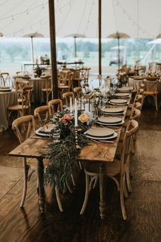 Rustic reception decor with gold candlesticks, lanterns, and green garlands | image by Grant Daniels Photography #texaswedding #centerpieces #reception #weddingreception #weddingreceptioninspo #receptioninspiration #receptiondecor #receptioninspo #sweethearttable #weddingbackdrop #finishingtouches #floraldesign #weddingdecor