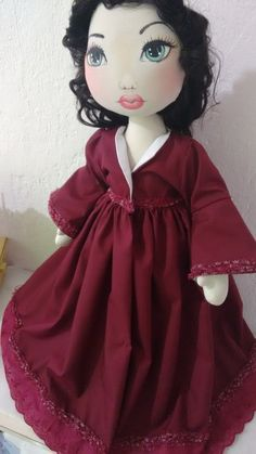 Boneca, minha versão de Scarlett O'hara <br>Mede 60 cm de altura, pesa 800 GR...é articulável, fica em pé sem suporte e pode sentar tbm. <br>Seu corpo é feito em algodão cru e revestido com manta acrílica, seu rosto é pintado a mão, cabelo dela é sintético de cor castanho escuro, o vestido é feito em tricoline e renda vinho, calçinha em tricoline vinho, um par de sapato feito em tecido.