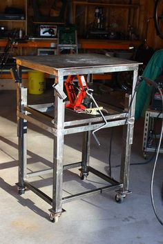 Adjustable Height Welding Table by mikes71sporty -- Homemade welding table constructed to facilitate MIG work. Constructed from angle and flat bar and featuring a steel plate top. Scissors jack positioned beneath the tabletop enables the overall height to be adjusted between 35-45 inches. Caster-mounted for increased mobility. http://www.homemadetools.net/homemade-adjustable-height-welding-table