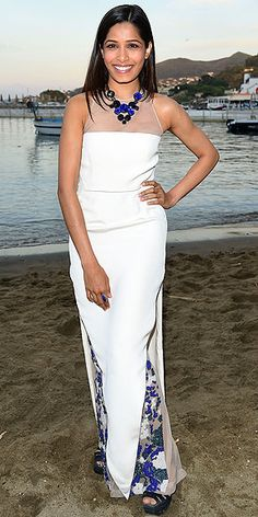 FREIDA PINTO Out in Ischia, Italy, for the film festival, the actress tries her hand at beach-friendly black-tie with a white Marios Schwab gown with a blue embroidered under-layer and sheer yoke.