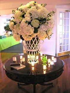 Hydrangeas for a wedding on a round dark wood table. Could be great for the guest book table!