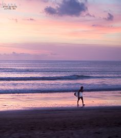 A surfer finishes his sunset surfing session on Kuta Beach, Bali. www.jayme.me
