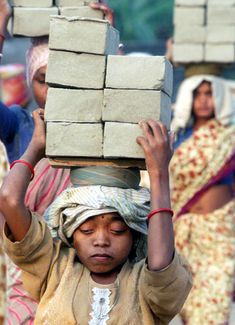 A child carries unbaked bricks to a kiln at a brick factory in Raichak, India, in December 2000. Scenes like this remain a fact of life in India, despite a longtime ban on hard labor by children.