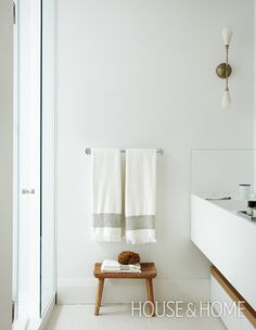 In this spa-like bathroom, a simple rustic bench adds natural texture and offers a convenient spot to stack towels. | Photographer: Virginia Macdonald | Designer: Sally Armstrong