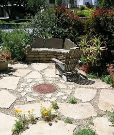 Patio Design Ideas: Front-Yard Flagstone Patio:  This Santa Monica front yard utilizes every inch of space for drought-tolerant and sustainable gardening, recycled pathways, repurposed art, and creative sitting areas, like this patio. Materials used are widely spaced pink / peach flagstone pavers with pea gravel in between. The circular metal object in the center is a vintage street-hole cover that is now the focus point of the patio. Simple, easy and original!