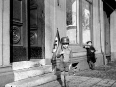 Once Upon A Time In War - small child waving Nazi flag while Jewish boy watches in the background. A reminder of a horrible time.