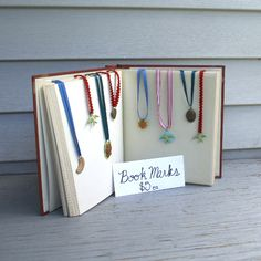 Flat items like bookmarks, cards, and some jewelry can be easily stored between the pages of virtually any book or photo album to create a great craft fair booth #display that also travels well.