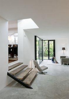 Superbe interrieurs, épuré industriel avec escalier aux marches en bois et fenêtres aluminium noir. Baie vitrée style industriel, atelier d'artiste.