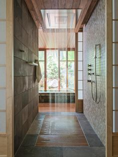 """a Japanese-inspired designer Susie Hoffman created a spectacular spa-inspired shower with a variety of water works. """"The high-volume water feature was intended to replicate the experience of being caught in a warm rain shower,""""says Koel. """"Materially, the balance of tile, translucent shoji screens, wood, and water seeks to complement the earthy materials used elsewhere in the project, while lending themselves to a quiet, personal, transformational spa experience."""""""