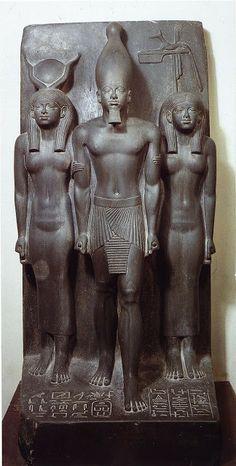 """Estatua del Faraón Mikerinos y su esposa, El Faraón Kefrén entronizado, Esta escultura exenta está realizada en piedra granítica, pizarra concretamente, y es pequeña, pues no llega al metro de altura. Nos muestra a tres personajes (el farón flanqueado por dos diosas), de ahí que reciba el nombre de """"tríada""""."""