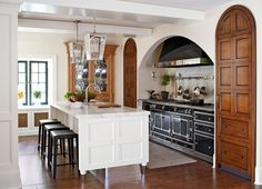 Arched cherry doors flank a handcrafted French stove in this European-style kitchen remodel. (Pantry on the left, refrigerator on the right.) By New Jersey kitchen designer Jim Dove; featured in Traditional Home.