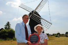 Lacey Green Windmill, July 2013. Johhn Wood, Chairman of the Institution's Engineering Heritage Committee presenting the plaque to Barbara Wallis, the widow of Christopher Wallis, who led the restoration project of the windmill.