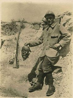 French soldier with severed German head, WWI (I don't think he actually severed it, he probably found it rotting somewhere)