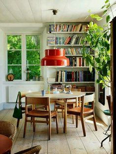 Dining room inspiration. White walls. Bookcase. Round wood table. Beautiful wooden chairs. Huge plant. Red vintage pendant lamp.