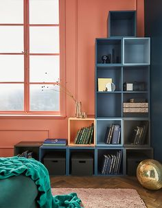 Modular cabinets like EKET from IKEA make it easy to build custom wall storage like this reverse L-shape against a corner. Shades of blue and grey tie the look together while keeping things interesting. A pop of light orange is playful, too.