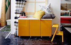 Ein Fensterplatz bestehend aus METOD Wandschränken mit Böden mit JÄRSTA Türen in Gelb auf Beinen. Darauf liegen viele bequeme Kissen.
