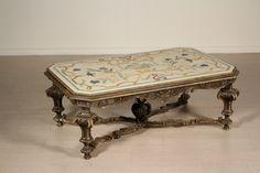 Gambe raccordate da crociera, piano in marmo chiaro decorato in policromia. Riccamente intagliato.