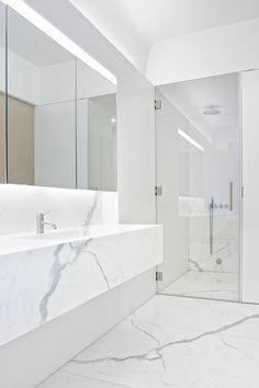jolie salle de bain en marbre blanc, grand miroir dans la salle de bain