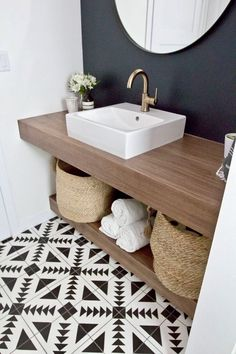 Bathroom - patterned tile floor + dark wall.