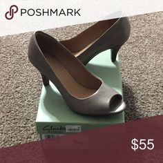 (Brand New, Never Worn) Clarks Artisan Heels *Price Lowered. Never Worn!! Traditional Peep-Toe pump with stacked, mid-height heel. Leather exterior with Rubber Sole... 8.5M Color: Platinum with Tan insole Clarks Shoes Heels