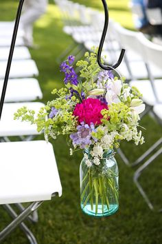 Blue Ball Mason Jars with wild flowers - hanging on hooks... would be pretty and easy to move for reception