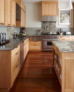 Maple cabinets with blue/green tile backsplash and gray (well, stainless steel) countertops.