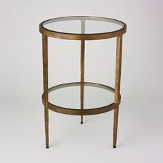 Two-tier iron table with clear glass top and shelf. Available with Gold finish or Braised Brass.