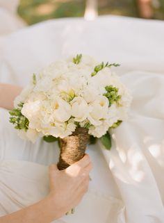 The bridal bouquet was created with white hydrangea, white freesia, white stock, white cabbage roses, white ranunculus, white patience cabbage roses, white fringed tulips, white parrot tulips, and green hypericum berry.
