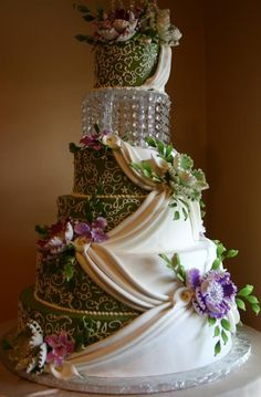 Gorgeous Indian Cake: green, gold, and white cover the cake with multiple colored flowers...Simply breath taking...Stunning.