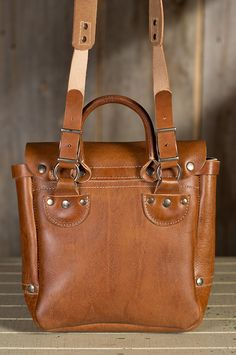 Carry your documents, your digital tablet, cell phone and wallet, with room to spare, in the Small Douglas Postal Bag. An updated U.S. Postman's bag, this 1930s inspired attaché exudes luxury with premium Italian leather that's vegetable tanned and unlined for a vintage style. Inside you'll find plenty of organized space that includes a wide zip pocket and cell phone pocket, all secured by the front flap that fastens with a hidden clasp.  A sturdy leather handle gives you comfortable hand…