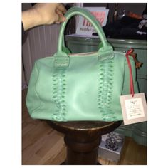 sophia c teal handbag. real italian leather w/ braid front detailing. zipper has brown tassel and bag comes with long brown detachable strap. lined w/ cream and brown striped canvas. bags has a very small spot of discoloration, not noticeable when worn (pictured) also a small piece of leather has come off due to being stored w/ other purses (pictured) other side is in perfect condition. lining has lip liner marks (pictured as best as possible) could possibly be cleaned, also not noticeable…