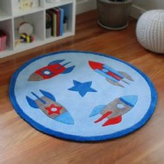 Blast Off Kids Rug from BugRugs.  This children's rug has a fun rocket-ship design in red and varying shades of blue.  Let your little one blast off to the stars with this whimsical floor rug.  Perfect for nurseries, bedrooms and playrooms.  Available in 1.2m diameter.