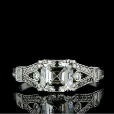 1.53 carat Asscher cut diamond. Smaller than mine but  love the four claw prongs and fancy open work gallery as well as the split shoulders.