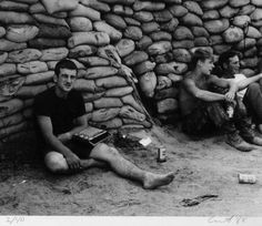 Christmas  Caption:  Off-duty soldiers sit against sandbags, drinking beer at Christmas, listening to the wireless radio.     Artist:  Steve Curtis  Date:  1968
