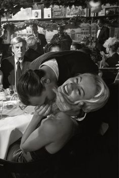 The late George Plimpton in the background, decidedly NOT amused by the amorous couple in the foreground. Elaine's, New York. Photo: Larry Fink.