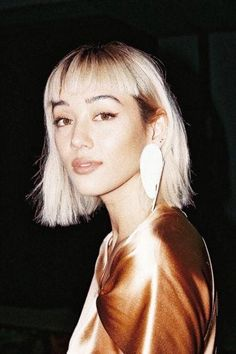 Types of bangs guide: Kim Jones with a bleach blonde long bob styled with a micro fringe, wearing a seashell earring with a satin orange top Blonde Hair With Fringe, Blonde Bob With Bangs, Long Bob Bangs, Lob Bangs, Blonde Curly Bob, Long Bob Styles, Short Hair Styles, Curly Bob Hairstyles, Fringe Hairstyles