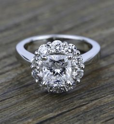 Ten round diamonds, depending on center stone size, are prong set in this striking white gold engagement ring setting, making your choice of center diamond the middle of a blooming flower.