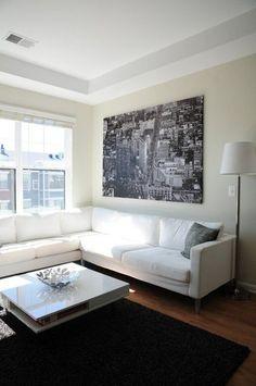 sala decorada com quadro grande, quadro gigante na decoração, quadro grande com fotografia urbana em preto e branco em cima do sofá, decoração minimalista, sofá branco e luminária de chçao branca