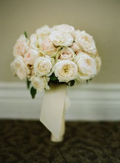 The bridesmaids will carry clutch bouquets of ivory garden roses, blush pink spray roses, and silver brunia wrapped in slate grey ribbon